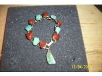 ladies vintage bracelet with blue and red marbly stones and hanging charm stone