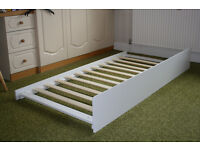 White wooden single trundle bed