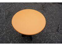 Circular wooden table suitable for garden use.