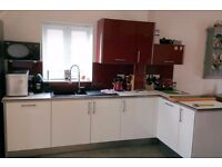 Wren high gloss red wall and white base kitchen units with white worktops