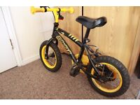 Boys Stinger Apollo bike with 12 inch wheels and a red helmet
