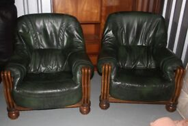 Two green leather arm chairs set in wooden frame