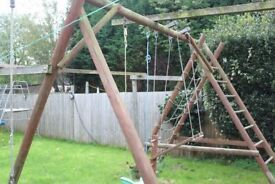 Large wooden climbing frame with swing, tire swing, seesaw and cargo climbing net