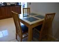 Small dining table with glass top and four chairs