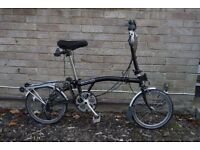 Brompton M6R folding bicycle with six speeds, rack, pump, mud guards, indicators and bag