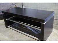Wooden TV stand with glass shelving for additional devices