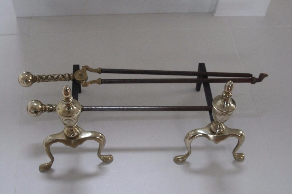 Pair of solid brass fire dogs, brass handle poker, and brass handle coal tongs