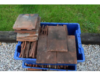 Red roofing tiles. 50 dark red weathered roofing tiles and approximately 50 Kent peg tiles