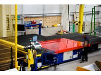 Glass Cutter for architectural glass manufacturing company working on busy factory floor