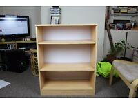 Small, light wood coloured bookcase with removable shelves and holes to alter shelf position