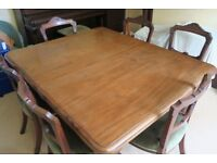 An extending dining table, maybe walnut, seating up to 12 people, & 6 chairs with upholstered seats