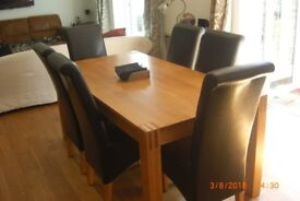 Six Faux Leather dark brown high scroll back dining chairs with oak veneer legs.