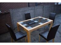 Glass table with wooden base and brown four faux leather chairs