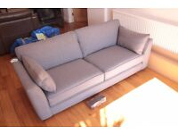 Brand New Sofa, Never Used - Grey, upholstered with dark wood feet.