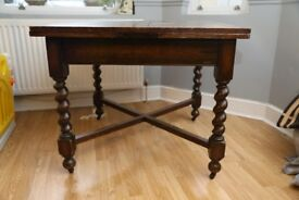 Antique extendable oak dining table with turned leg casters