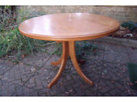 Round extendable dining table on centre column. Inlaid edge light teak colour.