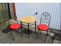 metal framed table with round wooden top and two metal chairs with padded seats