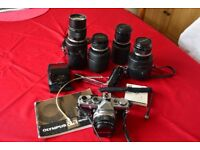 Olympus OM1n camera with a collection of lenses and attachments