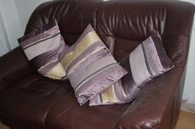 Two-seater leather sofa, matching leather armchair and footstool in good condition