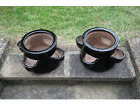 Two black glazed terracotta plant containers/pots