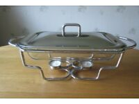 Heatproof glass serving dish with stainless steel lid and twin tealight warming stand.