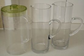 "2x 10"" high glass jugs. 1x plastic 9.5"" high plastic jug with lid"