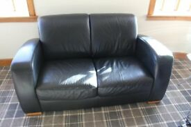 A pair of black Natuzzi leather 2 seater sofas in excellent condition