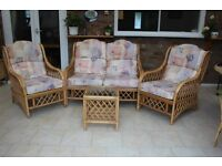 Conservatory cane settee and two armchairs, two coffee tables and storage unit with cupboard