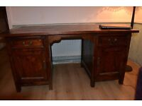 Large solid wood writing desk with drawers and cupboards and 5 piece self assembly.