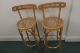 Tall, wooden-framed bar stools (115cm high) with backs and woven seats