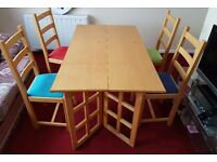 Wooden Kitchen/dinner table and 4 nice solid colourd chairs.