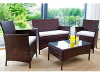Brown Rattan Garden furniture - cushioned two seater and two single chairs with glass topped table