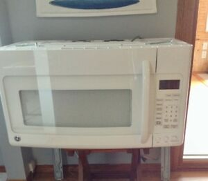 White microwave, over stove with fan