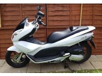 White scooter in excellent condition, automatic, electric start, 100mpg, helmet storage under seat