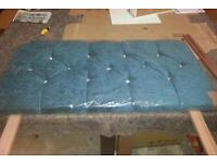 A brand new turquoise fabric single headboard with dimoni effect detail.