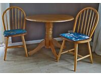 Drop leaf round dining table and two matching chairs in excellent condition.