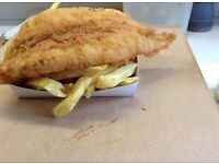 Part time fish fryer in traditional style fish and chip shop with tearoom