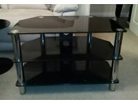 TV unit in black glass with silver legs- ideal for a corner but fine anywhere. In good condition.