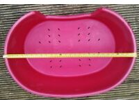 RED PLASTIC OVAL DOG BASKET (28 INCHES AT WIDEST POINT)
