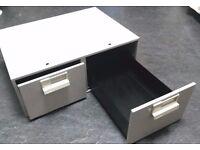 Grey metal twin drawer unit.