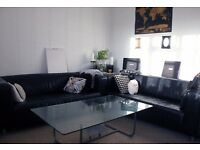 Three/ Four Seater Black Leather Sofas (TWO SOFAS) and Free Glass Coffee Table