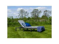 new rattan effect sun lounger still in box. with cushions