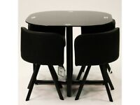 Black gloss hideaway dining table and chairs by Charles Jacobs from Wayfair