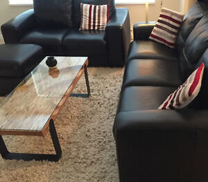 Black leather couches and ottoman