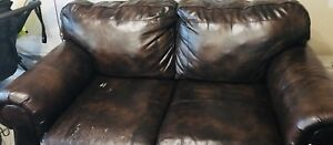 A brown bonded leather couch and love seat