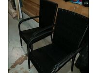 A brand new pair of black high back patio chairs.