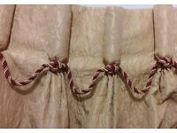 Heavy gold brocade curtains with cranberry trimming.