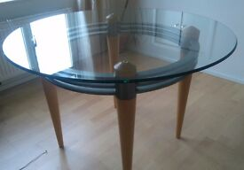 Contemporary glass dining table with solid wood legs