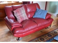 Red leather 2 seater sofa.