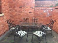Garden/patio glass table and 6 chairs black metal chairs with cushions